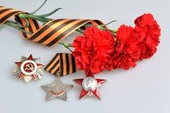 Τα κόκκινα λουλούδια έδεσαν με την κορδέλλα Αγίου George, διαταγές του μεγάλου πατριωτικού πολέμου Στοκ Εικόνα