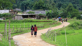 Τα κόκκινα παιδιά Dao περπατούν επάνω στο χωριό τους Στοκ Φωτογραφίες