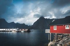 Τα κόκκινα σπίτια ουράνιων τόξων ofer rorbuer Reine σε Lofoten, Νορβηγία με το κόκκινο rorbu στεγάζουν, σύννεφα, βροχερός μπλε ου στοκ φωτογραφίες