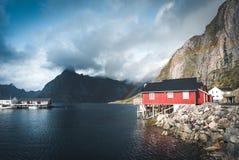 Τα κόκκινα σπίτια ουράνιων τόξων ofer rorbuer Reine σε Lofoten, Νορβηγία με το κόκκινο rorbu στεγάζουν, σύννεφα, βροχερός μπλε ου στοκ εικόνα με δικαίωμα ελεύθερης χρήσης