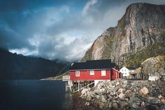 Τα κόκκινα σπίτια ουράνιων τόξων ofer rorbuer Reine σε Lofoten, Νορβηγία με το κόκκινο rorbu στεγάζουν, σύννεφα, βροχερός μπλε ου στοκ εικόνες