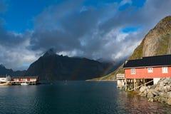 Τα κόκκινα σπίτια ουράνιων τόξων ofer rorbuer Reine σε Lofoten, Νορβηγία με το κόκκινο rorbu στεγάζουν, σύννεφα, βροχερός μπλε ου στοκ φωτογραφία με δικαίωμα ελεύθερης χρήσης