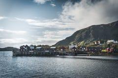 Τα κόκκινα σπίτια ουράνιων τόξων ofer rorbuer Reine σε Lofoten, Νορβηγία με το κόκκινο rorbu στεγάζουν, σύννεφα, βροχερός μπλε ου στοκ εικόνα
