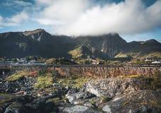 Τα κόκκινα σπίτια ουράνιων τόξων ofer rorbuer Reine σε Lofoten, Νορβηγία με το κόκκινο rorbu στεγάζουν, σύννεφα, βροχερός μπλε ου στοκ εικόνες με δικαίωμα ελεύθερης χρήσης