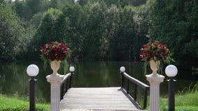 Τα κόκκινα τριαντάφυλλα ανθίζουν τις ανθοδέσμες σύνθεσης στη γαμήλια τελετή στην επαρχία στη θερινή ηλιόλουστη ημέρα απόθεμα βίντεο