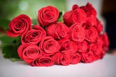 Τα κόκκινα τριαντάφυλλα ανθοδεσμών στον πίνακα κλείνουν επάνω Υπόβαθρο Στοκ Εικόνες