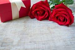 Τα κόκκινα τριαντάφυλλα με το κόκκινο κιβώτιο δώρων επάνω συνδεδεμένο διάνυσμα βαλεντίνων απεικόνισης s δύο καρδιών ημέρας Στοκ εικόνα με δικαίωμα ελεύθερης χρήσης
