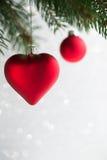 Τα κόκκινα Χριστούγεννα διακοσμούν την καρδιά και η σφαίρα στο χριστουγεννιάτικο δέντρο ακτινοβολεί επάνω bokeh υπόβαθρο Στοκ Εικόνα