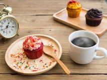 Τα κόκκινα cupcakes που τίθενται σε ένα σφαιρικό ξύλινο πιάτο εκτός από του cupcake έχουν το εκλεκτής ποιότητας ξυπνητήρι Στοκ Φωτογραφίες