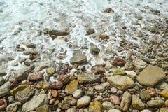 Τα κύματα θάλασσας, αφρός θάλασσας, χωρίζουν στις παράκτιες πέτρες Στοκ Εικόνα
