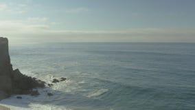 Τα κύματα και οι βράχοι ενός απότομου βράχου στην παραλία απόθεμα βίντεο