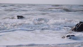 Τα κύματα καλύπτουν τις μαύρες πέτρες γρανίτη στη θάλασσα ενάντια στον ουρανό απόθεμα βίντεο