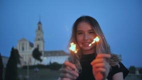 Τα κύματα κοριτσιών τα χέρια της με τα sparklers στο υπόβαθρο της πόλης βραδιού φιλμ μικρού μήκους