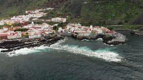 Εναέριος πυροβολισμός Μικρή πόλη στη βάση του βουνού Ηφαιστειακή ακτή του ωκεανού Τα κύματα κτυπούν στον παράκτιο σκόπελο και απόθεμα βίντεο