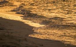 Τα κύματα πλένουν την ακτή στο ηλιοβασίλεμα στοκ εικόνα