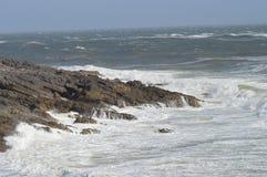 Τα κύματα που σπάζουν πέρα από τους βράχους μουρμουρίζουν πλησίον, Ουαλία, UK Στοκ Φωτογραφία