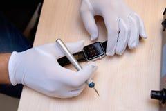 Τα κύρια χέρια ` s που επισκευάζουν το ηλεκτρονικό ρολόι Στοκ φωτογραφία με δικαίωμα ελεύθερης χρήσης