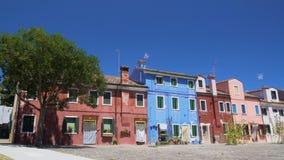Τα λαμπρά χρωματισμένα σπίτια με τις πόρτες και τα παράθυρα κλείνουν, καυτό καλοκαίρι σε ηλιόλουστο Burano φιλμ μικρού μήκους