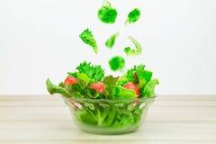 Τα λαχανικά σαλάτας που εμπίπτουν στο γυαλί λαχανικών σαλάτας κυλούν στον ξύλινο πίνακα στην άσπρη πλάγια όψη υποβάθρου Στοκ φωτογραφία με δικαίωμα ελεύθερης χρήσης