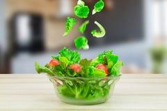 Τα λαχανικά σαλάτας που εμπίπτουν στο γυαλί λαχανικών σαλάτας κυλούν στον ξύλινο πίνακα στο θολωμένο υπόβαθρο κουζινών Στοκ εικόνα με δικαίωμα ελεύθερης χρήσης