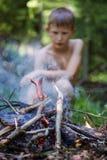Τα λουκάνικα τηγανητών αγοριών σε μια πυρκαγιά Το αγόρι στο δάσος στοκ εικόνες με δικαίωμα ελεύθερης χρήσης