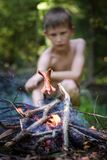 Τα λουκάνικα τηγανητών αγοριών σε μια πυρκαγιά Το αγόρι στο δάσος στοκ εικόνες