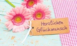 Τα λουλούδια και η κάρτα ευχετήριων καρτών με το γερμανικό κείμενο, Herzlichen Glueckwunsch, σημαίνουν τα συγχαρητήρια στοκ φωτογραφία με δικαίωμα ελεύθερης χρήσης