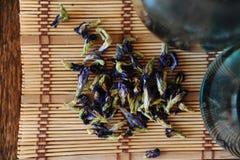 Τα λουλούδια του ταϊλανδικού μπλε τσαγιού Anchan είναι διεσπαρμένα σε μια κινηματογράφηση σε πρώτο πλάνο χαλιών μπαμπού Στοκ Εικόνα