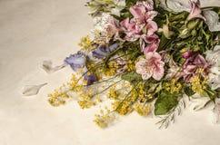 Τα λουλούδια Alstroemeria με την πορφυρή ίριδα και τα κίτρινα λουλούδια του άγριου ραδικιού βρίσκονται διαγωνίως Στοκ εικόνα με δικαίωμα ελεύθερης χρήσης