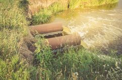 Τα λύματα από τον υπόνομο μολύνουν μια ροή του νερού λιμνών/αποβλήτων από τον υδροσωλήνα στη λίμνη στην ανατολή στοκ εικόνες