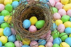 Τα μέρη των αυγών Πάσχας καραμελών περιβάλλουν τη φωλιά ενός πουλιού. Στοκ εικόνες με δικαίωμα ελεύθερης χρήσης