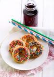 Τα μίνι donuts με το γλυκό ψεκάζουν στοκ εικόνες