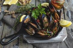 Τα μαγειρευμένα μύδια μαλακίων θαλασσινών στο σίδηρο φιλτράρουν τη μερίδα με το λεμόνι και το καρύκευμα στοκ εικόνα