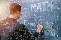 Τα μαθηματικά διδασκαλίας, δεξιά κρατούν την κιμωλία Η γραφική παράσταση δημιουργεί το χαλί στοκ φωτογραφίες