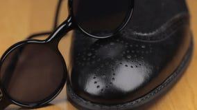 Τα μαύρα γυαλιά ηλίου είναι στα παπούτσια μαύρων ` s Μετακινηθείτε τον πυροβολισμό απόθεμα βίντεο