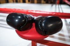 Τα μαύρα εγκιβωτίζοντας γάντια είναι στην εγκιβωτίζοντας κόκκινη καρέκλα Εγκιβωτίζοντας δαχτυλίδι Fi Στοκ φωτογραφία με δικαίωμα ελεύθερης χρήσης