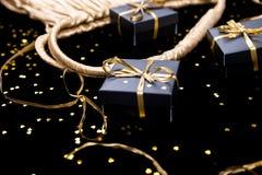 Τα μαύρα κιβώτια δώρων με τη χρυσή κορδέλλα λαϊκή έξω από τη χρυσή τσάντα λάμπουν επάνω υπόβαθρο Στοκ εικόνα με δικαίωμα ελεύθερης χρήσης