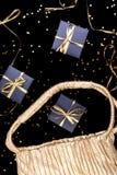 Τα μαύρα κιβώτια δώρων με τη χρυσή κορδέλλα λαϊκή έξω από τη χρυσή τσάντα λάμπουν επάνω υπόβαθρο Επίπεδος βάλτε Στοκ εικόνα με δικαίωμα ελεύθερης χρήσης