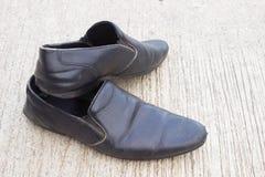 Τα μαύρα παπούτσια δέρματος στο τσιμέντο με το διάστημα αντιγράφων για γράφουν κάθε πράγμα, παλαιά μαύρα παπούτσια Στοκ Εικόνες