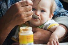 Τα μεγάλα τραχιά χέρια υποστηρίζουν ήπια το μωρό και ταΐζονται με ένα κουτάλι στοκ φωτογραφίες με δικαίωμα ελεύθερης χρήσης