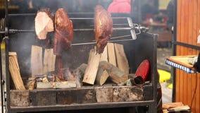 Τα μεγάλα χοντρά κομμάτια των εύγευστων ζαμπόν χοιρινού κρέατος που μαγειρεύονται ανοίγουν πυρ Τα τρόφιμα οδών Τρόφιμα υπαίθρια Σ φιλμ μικρού μήκους