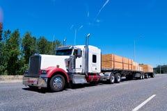 Τα μεγάλα εγκαταστάσεων γεώτρησης κλασικά ημι ρυμουλκά κρεβατιών φορτηγών επίπεδα φέρνουν την ξυλεία Στοκ Εικόνες