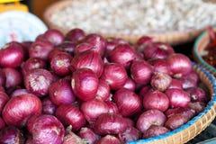 Τα μεγάλα κόκκινα κρεμμύδια στο καλάθι για πωλούν Στοκ Εικόνες
