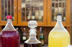 Τα μεγάλα μπουκάλια των φρούτων μούρων πίνουν τα εθνικά ηδύποτα στον καφέ σε μια έκθεση οδών Στοκ φωτογραφία με δικαίωμα ελεύθερης χρήσης
