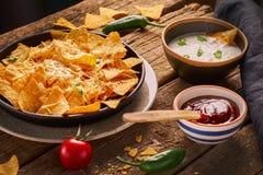 Τα μεξικάνικα nachos εξυπηρέτησαν με το λειωμένο τυρί, ποικιλία των εμβυθίσεων, ψυχρή, ντομάτες, αγροτικός ξύλινος πίνακας στοκ εικόνα με δικαίωμα ελεύθερης χρήσης