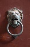 Τα μεσαιωνικά ρόπτρα πορτών σε μια μορφή λιονταριού σιδήρου διευθύνουν στο κόκκινο backgro Στοκ φωτογραφίες με δικαίωμα ελεύθερης χρήσης