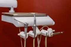 Τα μεταλλικά εργαλεία οδοντιάτρων κλείνουν επάνω σε μια καρέκλα οδοντιάτρων στον κόκκινο τόνο κλινικών οδοντιάτρων Στοκ Φωτογραφίες
