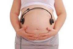 τα μελλοντικά ακουστικά μωρών αυτή ακούνε έγκυο στομάχι μουσικής τη γυναίκα Στοκ Εικόνες