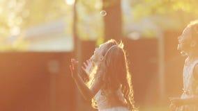 Τα μικρά ευρωπαϊκά παιδιά πηδούν και παίζουν με τις φυσαλίδες σαπουνιών σε ένα φως ηλιοβασιλέματος Φλόγα φακών, εξωτερικός πυροβο απόθεμα βίντεο