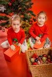Τα μικρά κορίτσια ανοίγουν τα δώρα τους Στοκ Φωτογραφίες